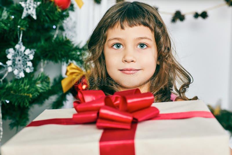 Bambina sveglia allegra con il presente Il bambino tiene un contenitore di regalo vicino all'albero di Natale all'interno immagine stock libera da diritti