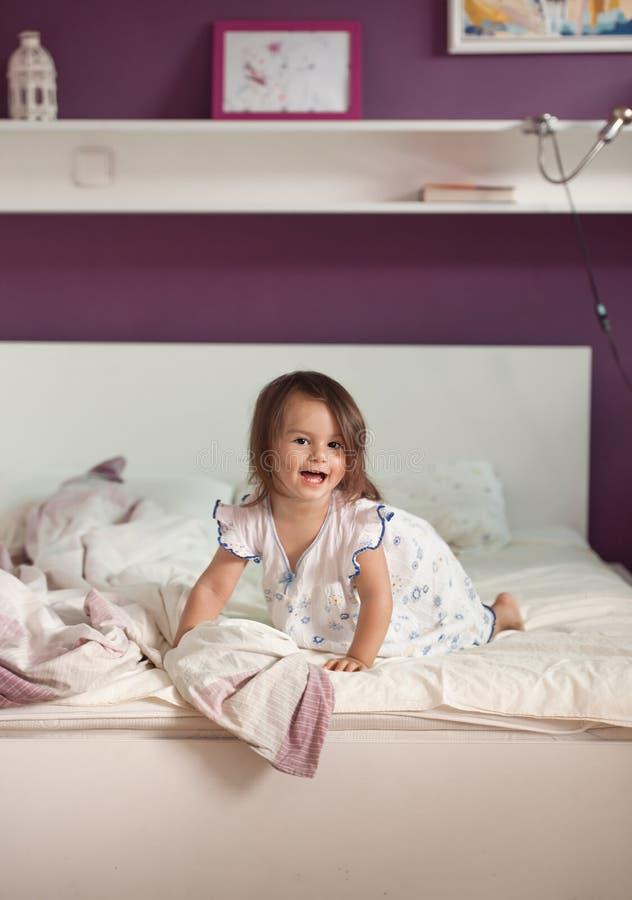 Bambina sveglia in camicia da notte sul letto di mattina fotografia stock libera da diritti