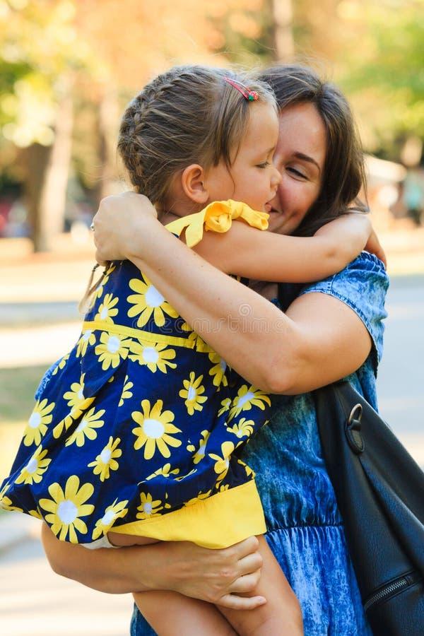 Bambina sveglia che abbraccia il suo colpo all'aperto della madre in parco fotografie stock