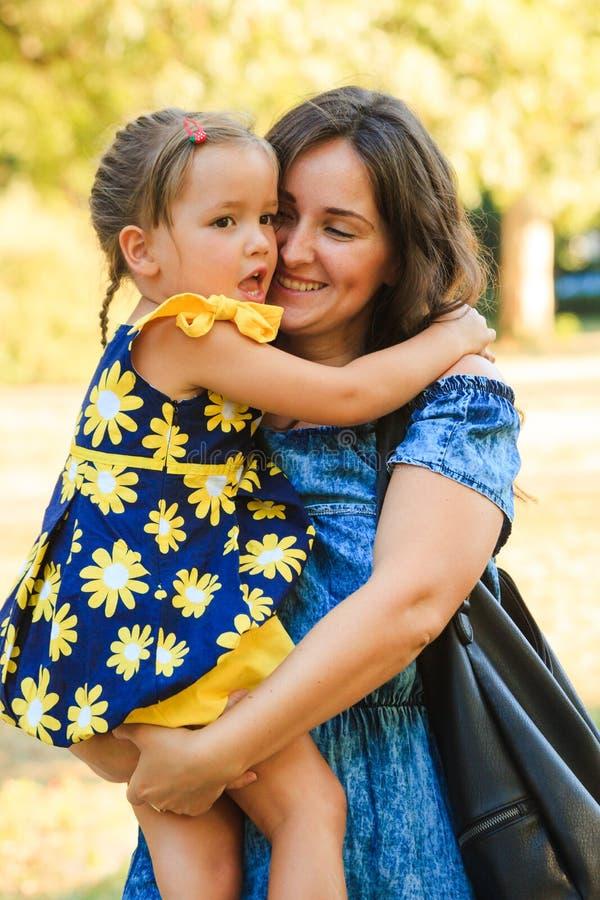 Bambina sveglia che abbraccia il suo colpo all'aperto della madre in parco fotografia stock
