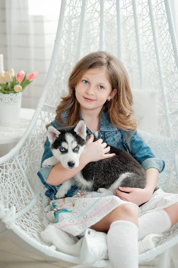 Bambina sveglia che abbraccia un cucciolo del husky su un fondo bianco Simbolo del nuovo anno 2018 immagini stock