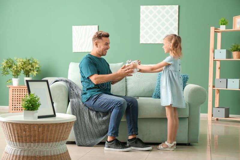 Bambina sveglia che accoglie il suo papà con la festa del papà a casa immagini stock