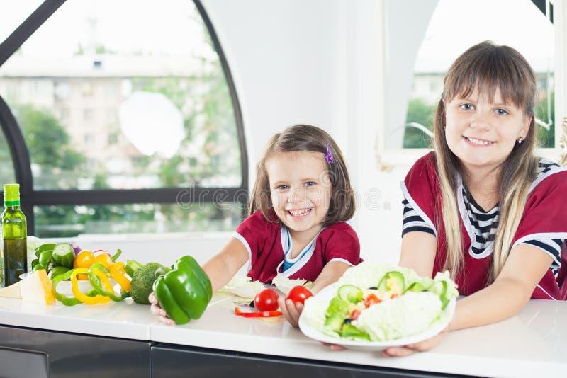 Bambina sveglia che cucina con sua sorella, alimento sano fotografia stock