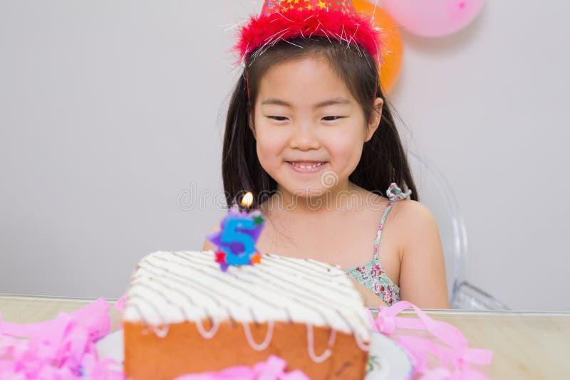Bambina sveglia che esamina la sua festa di compleanno immagine stock