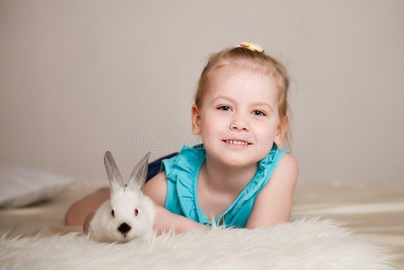 Bambina sveglia che gioca con i conigli bianchi immagini stock