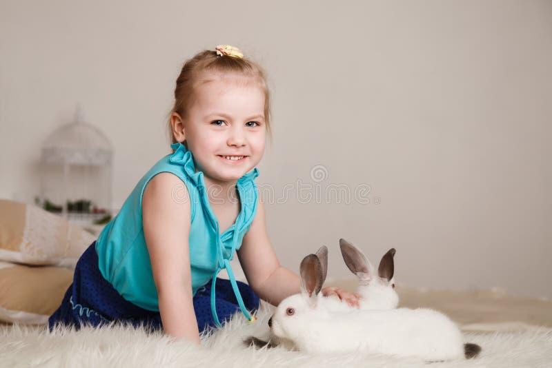 Bambina sveglia che gioca con i conigli bianchi immagine stock libera da diritti