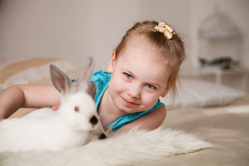 Bambina sveglia che gioca con i conigli bianchi fotografia stock