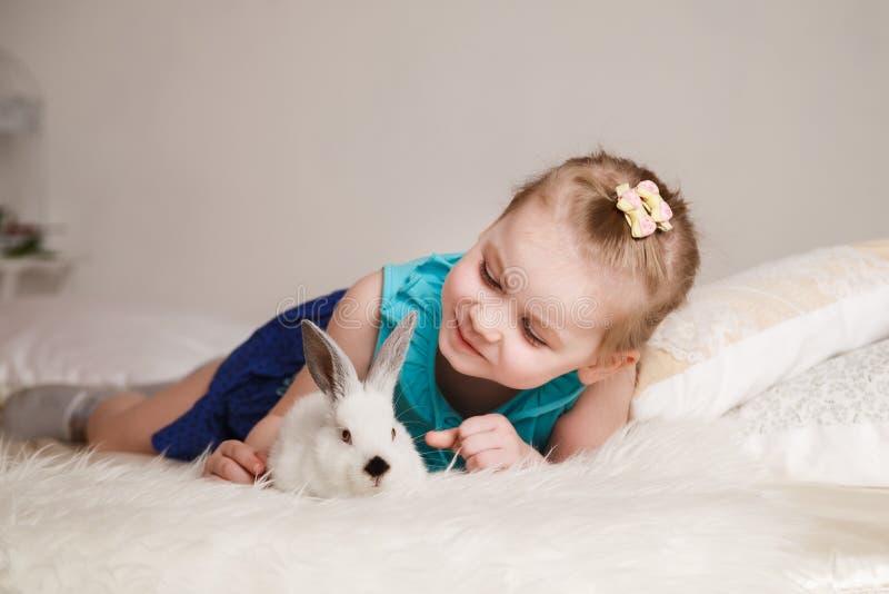 Bambina sveglia che gioca con i conigli bianchi immagini stock libere da diritti