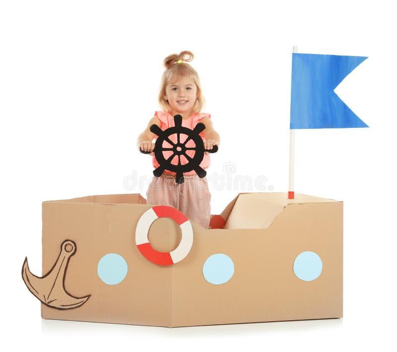 Bambina sveglia che gioca con la nave del cartone immagini stock