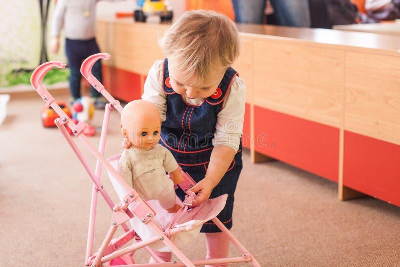 Bambina sveglia che gioca con la sua bambola fotografia stock