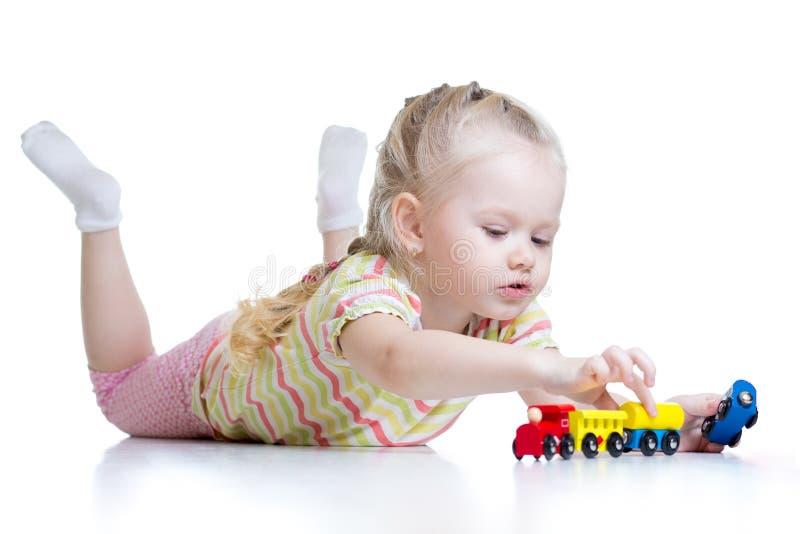 Bambina sveglia che gioca i treni isolati sopra bianco immagini stock libere da diritti