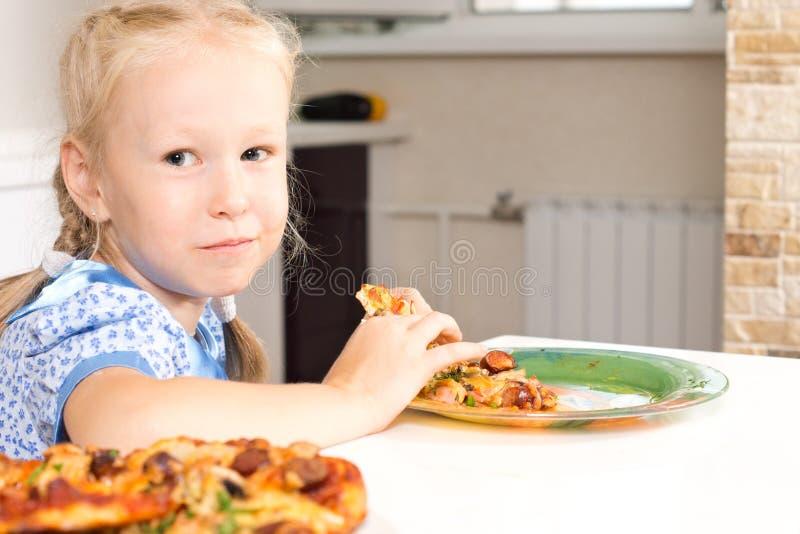 Bambina sveglia che gode di una pizza casalinga fotografia stock