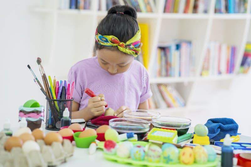 Bambina sveglia che impara dipingere le uova di Pasqua immagine stock libera da diritti