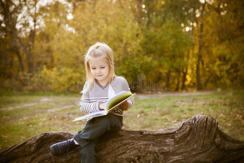 Bambina sveglia che legge un libro fotografia stock