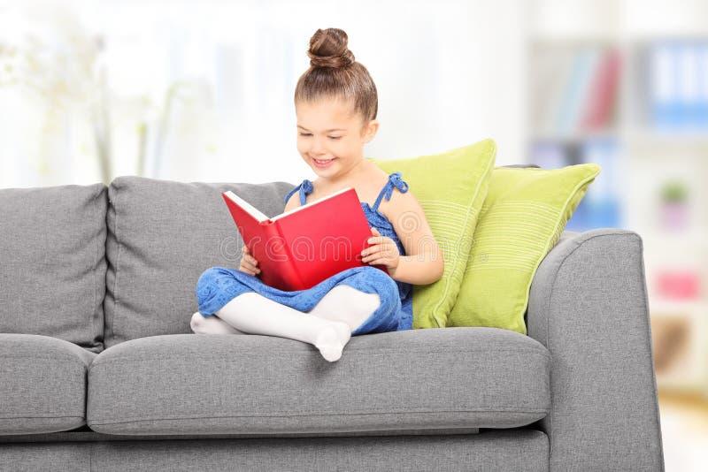 Bambina sveglia che legge un libro nel salone fotografia stock