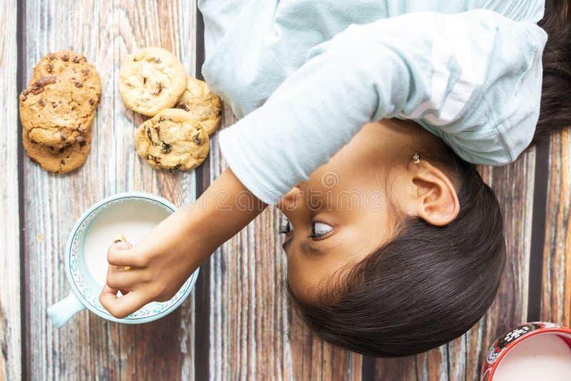 Bambina sveglia che mangia i biscotti con latte immagine stock libera da diritti