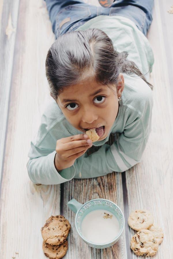 Bambina sveglia che mangia i biscotti con latte fotografie stock libere da diritti