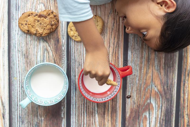 Bambina sveglia che mangia i biscotti con latte fotografia stock libera da diritti
