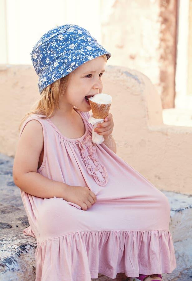 Bambina sveglia che mangia il gelato all'aperto immagini stock libere da diritti