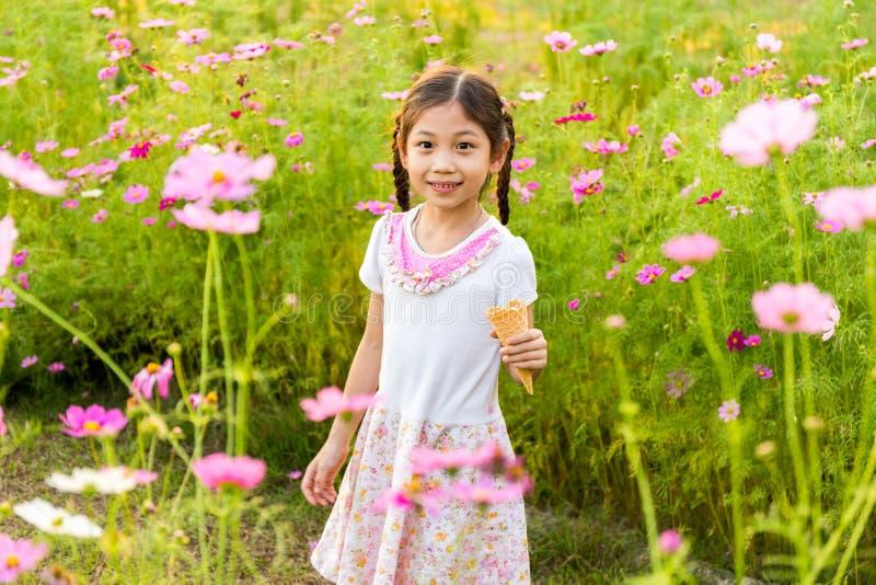Bambina sveglia che mangia il gelato nel campo dei fiori rosa fotografie stock libere da diritti