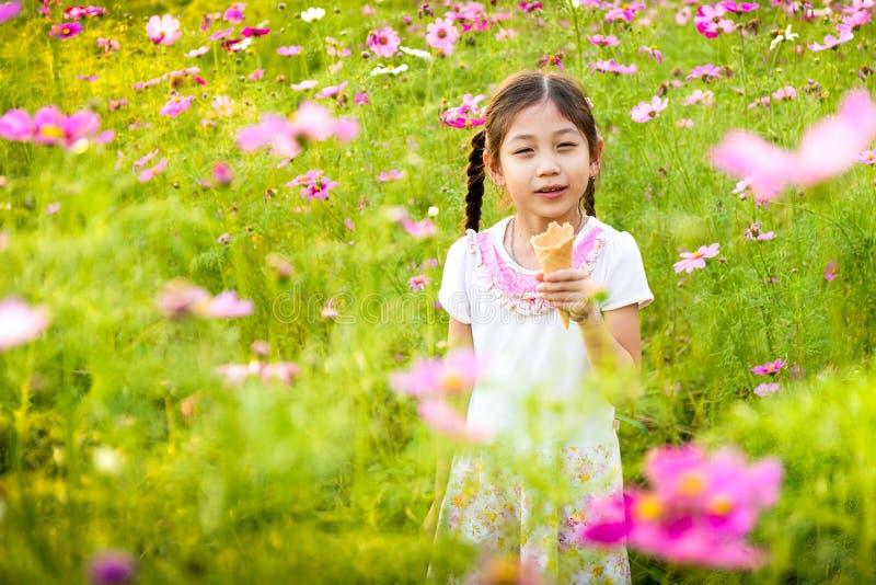 Bambina sveglia che mangia il gelato nel campo dei fiori rosa fotografia stock libera da diritti