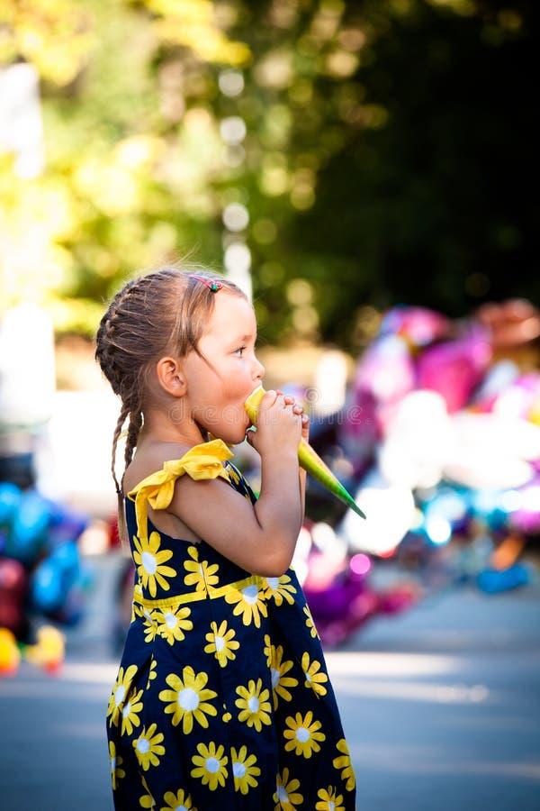 Bambina sveglia che mangia il gelato nel giorno di estate del parco fotografia stock
