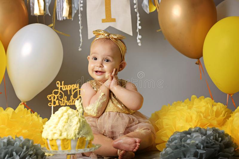 Bambina sveglia che mangia la sua prima torta di compleanno fotografie stock