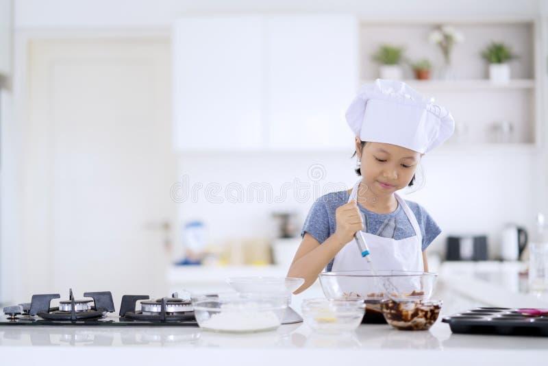 Bambina sveglia che mescola la pasta del biscotto immagini stock