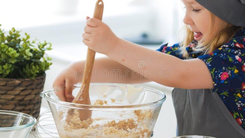 Bambina sveglia che mescola la pasta per i biscotti con il cucchiaio di legno in ciotola di vetro fotografia stock libera da diritti
