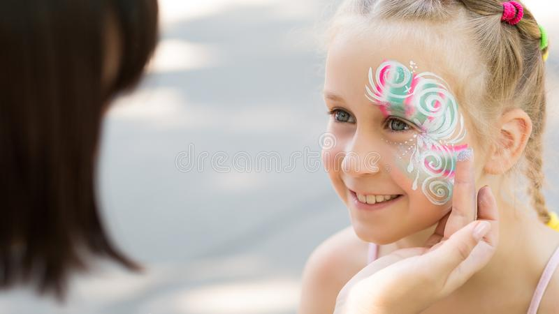 Bambina sveglia che ottiene il suo fronte dipinto in parco immagini stock libere da diritti