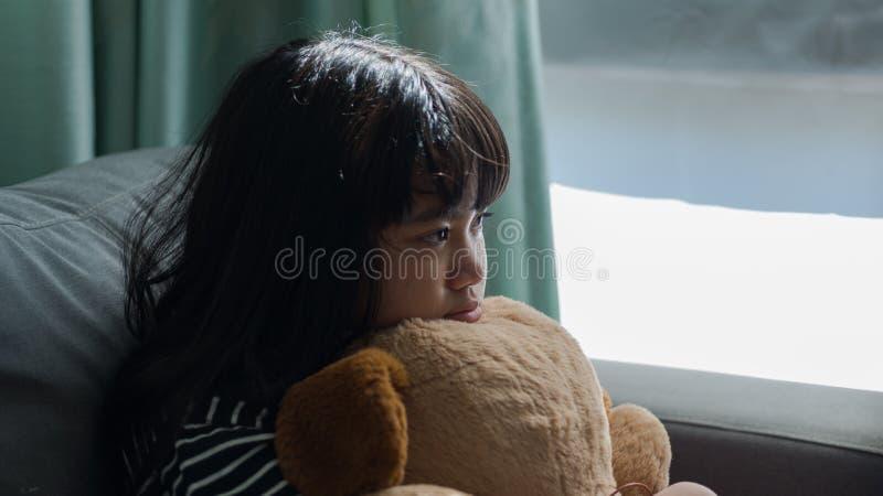 Bambina sveglia che pensa e che tiene una bambola, una preoccupazione e un triste sopra immagini stock