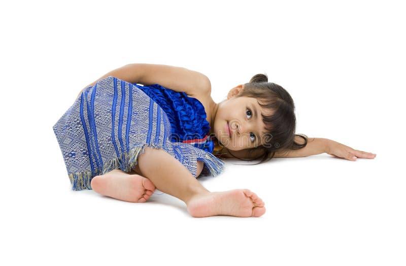 Bambina sveglia che pone sul pavimento immagini stock