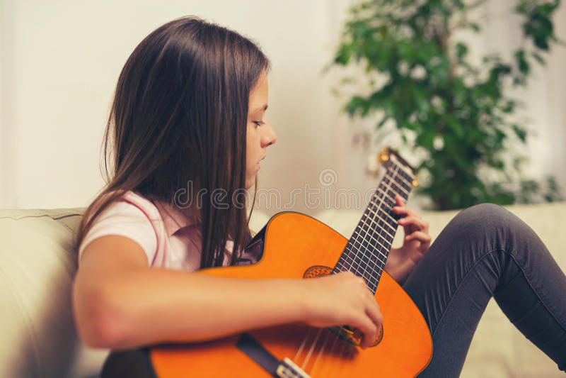 Bambina sveglia che pratica le sue lezioni della chitarra immagini stock libere da diritti