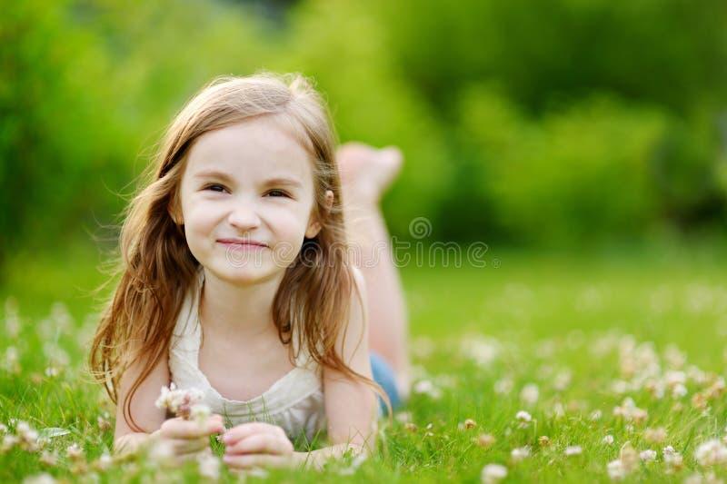 Bambina sveglia che risiede nell'erba fotografie stock libere da diritti