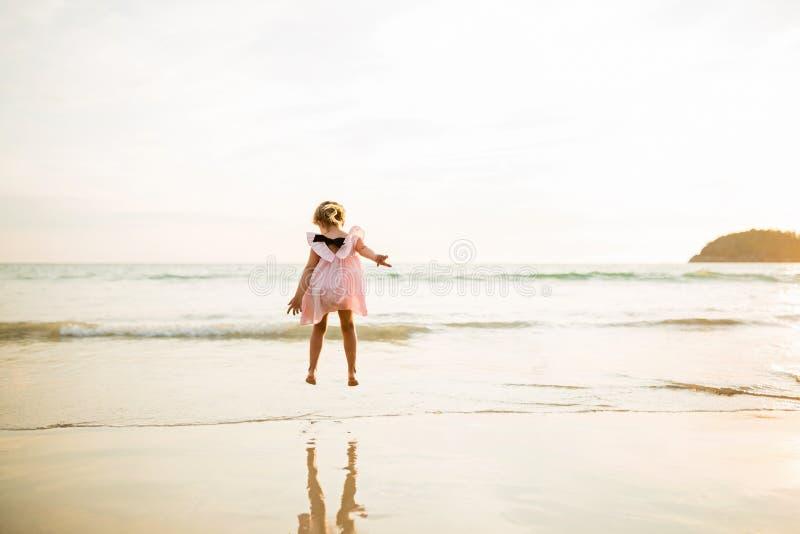 Bambina sveglia che salta sulla spiaggia Tempo di tramonto Bambino divertendosi nella vacanza di festa con la gioventù luminosa d fotografia stock
