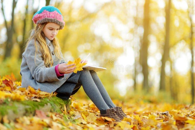 Bambina sveglia che schizza esterno il bello giorno di autunno Bambino felice che gioca nel parco di autunno Disegno del bambino  fotografia stock