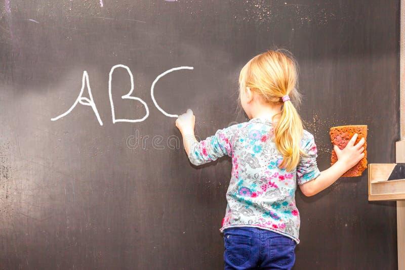 Bambina sveglia che scrive ABC sulla lavagna immagini stock libere da diritti