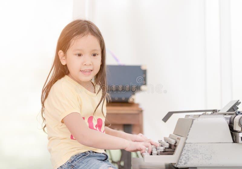 Bambina sveglia che scrive sulla retro macchina da scrivere immagini stock libere da diritti