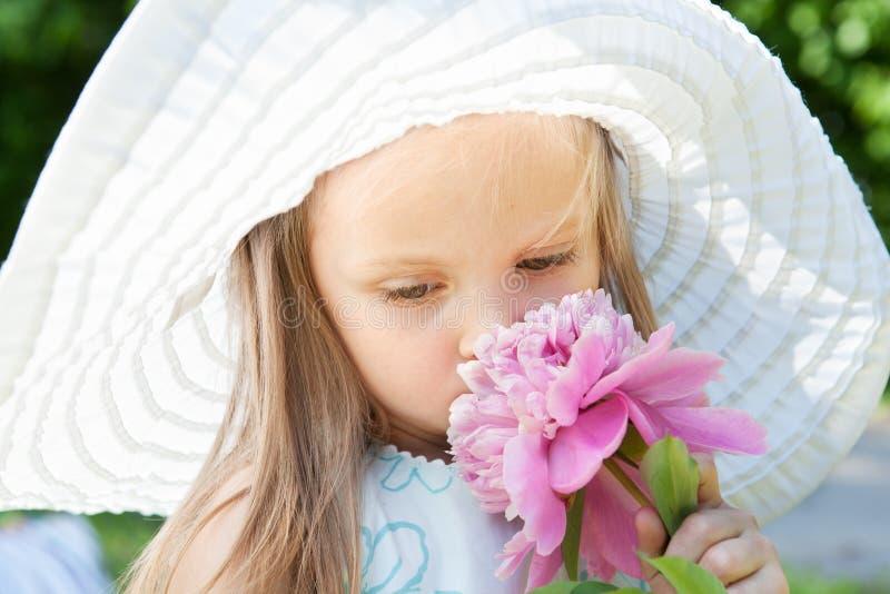 Bambina sveglia che sente l'odore di un fiore immagini stock libere da diritti