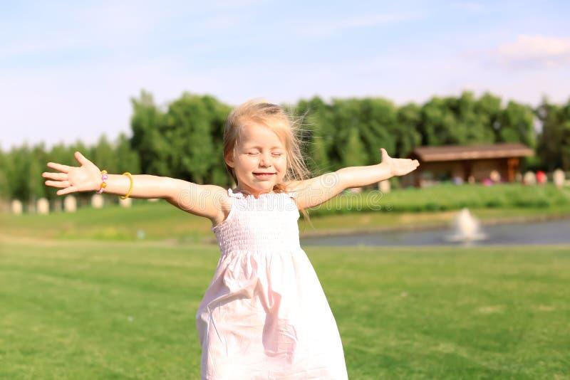 Bambina sveglia che si rilassa nel parco il giorno soleggiato fotografie stock libere da diritti