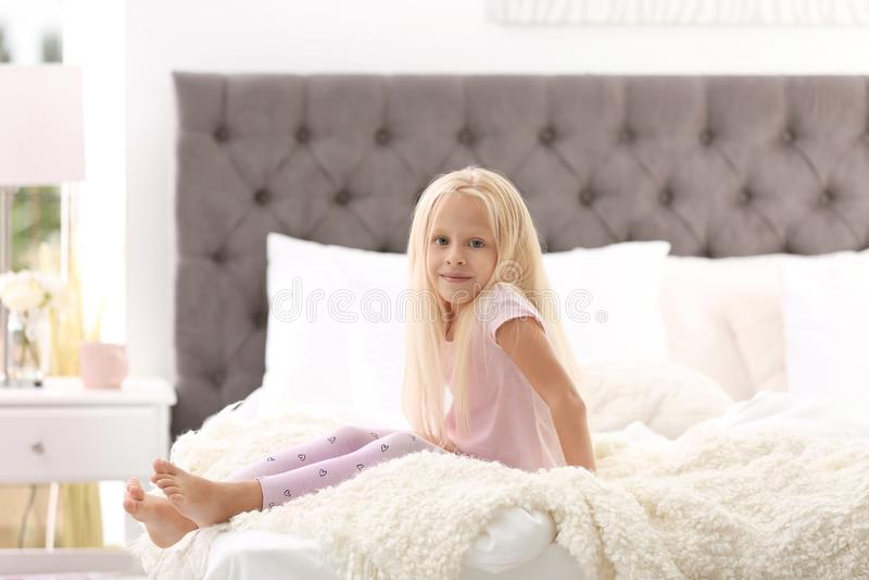 Bambina sveglia che si siede sul letto con i cuscini fotografia stock libera da diritti