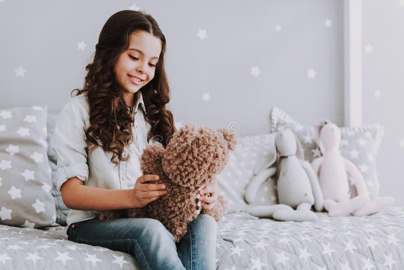 Bambina sveglia che si siede sul letto che tiene Teddy Bear immagine stock