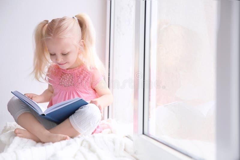 Bambina sveglia che si siede sul libro di lettura e di davanzale fotografia stock libera da diritti