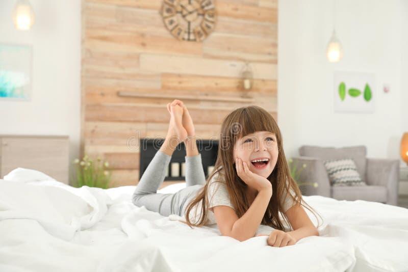 Bambina sveglia che si trova sul letto fotografie stock libere da diritti