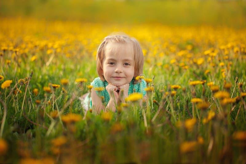 Bambina sveglia che si trova sul prato giallo del dente di leone nel giorno di estate fotografie stock libere da diritti