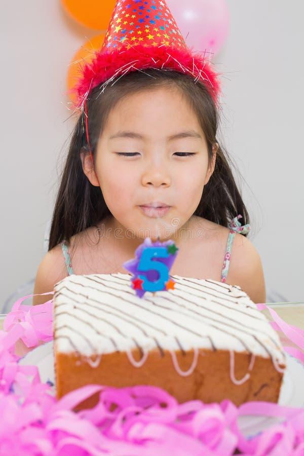 Bambina sveglia che soffia la sua torta di compleanno immagine stock