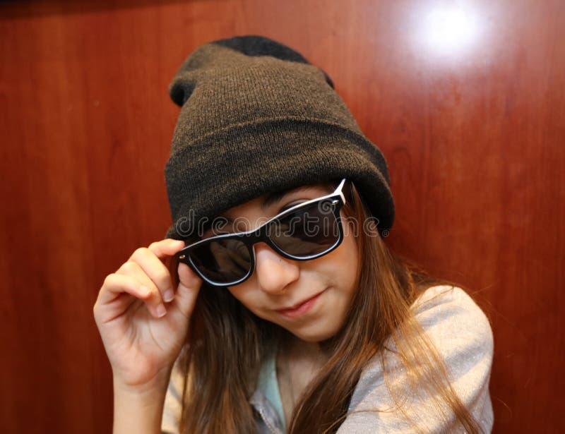 Bambina sveglia che sorride indossando gli occhiali da sole bianchi e neri fotografie stock