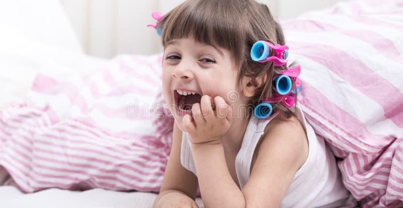 Bambina sveglia che sorride mentre trovandosi in un letto bianco accogliente immagini stock