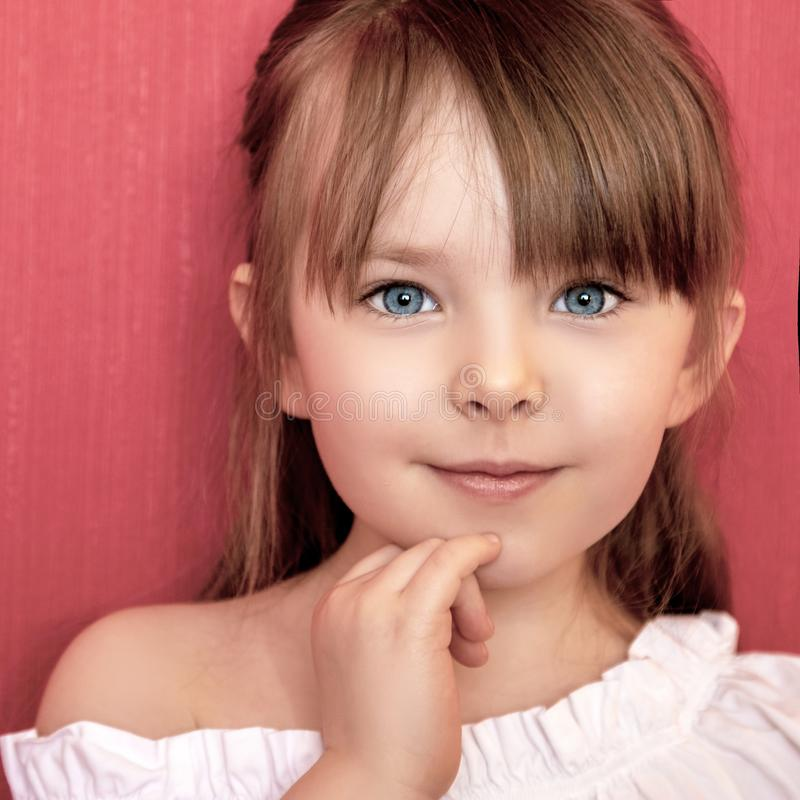 Bambina sveglia che sorride sopra il fondo rosa luminoso immagine stock libera da diritti