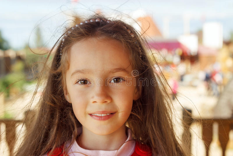Bambina sveglia che sorride in una fine del parco su immagine stock